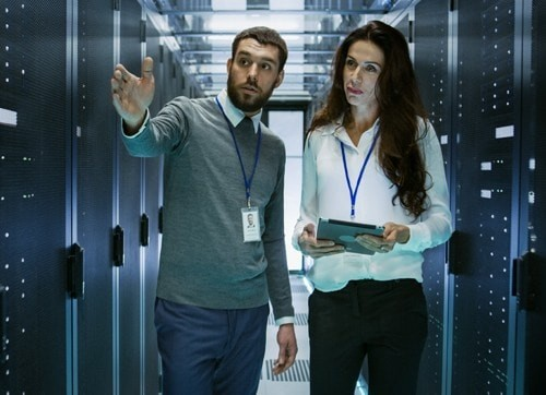Man and woman walking through server room